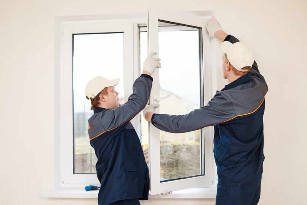 construction workers installing glass window indoor